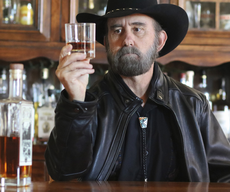 A Bearded Cowboy in Black Sitting Alone in a Saloon Contemplates His Whiskey Banco de Imagens