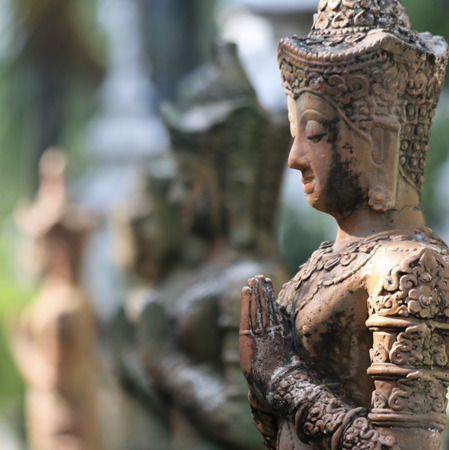 A Line of Praying Buddha Statues in the Ancient City of Wiang Kum Kam just south of Chiang Mai, Thailand.