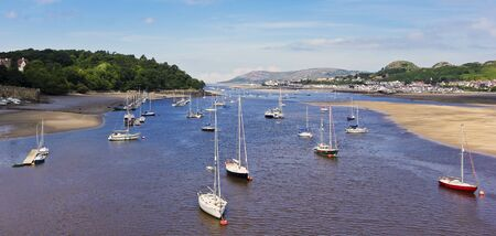 Boats moored at low tide near Conwy Castle in Conwy, Wales, Great Britain, United Kingdom.