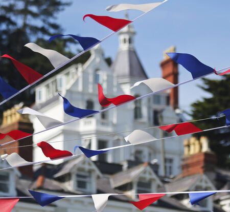A Bunting of Red, White and Blue Fourth of July Flags, Victorian Architecture Behind, Main Street, Anytown, USA