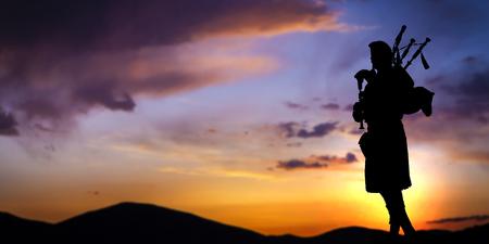 ドラマチックな夕焼け空に対してシルエットのバグパイプ プレーヤー
