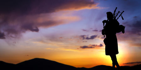 Bagpipe player in silhouette against dramatic sunset sky