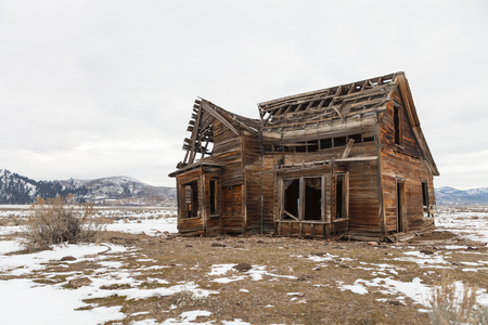 Old abandoned farm house in winter with snow.