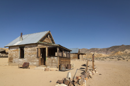 the miners: Abandoned ghost town home or shack in the Nevada Desert under clear blue skies.