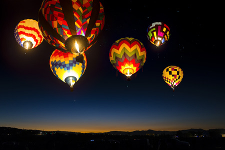 Colorful hot air balloons at dawn lit up in the sky. Stock Photo