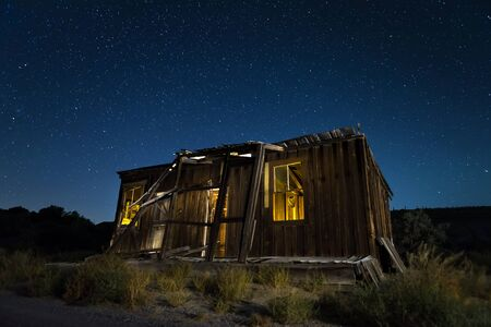 Old abandoned shack at night under a starry Nevada sky. Stock Photo