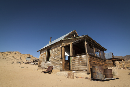 Abandoned ghost town home or shack in the Nevada Desert under clear blue skies.