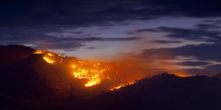 夕暮れ時の山火事を燃焼