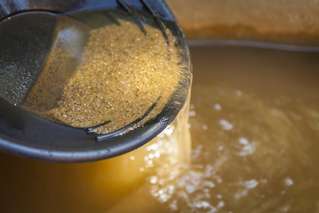 Primo piano d'oro panning padella con setacciare la sabbia. Profondità di campo con particolare attenzione sulla sabbia che scorre sul bordo della padella in acqua.