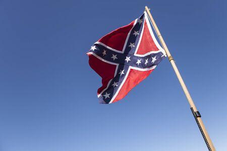 Confederate Flag on pole over blue sky. Stock Photo