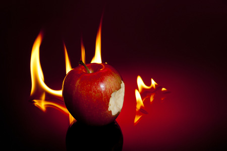 sinful: One sinful bite from apple with flames