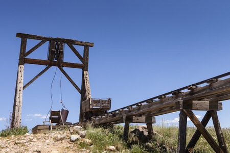 trestle: Old mining ore cart on trestle with head frame under blue sky.
