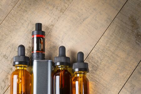 atomizer: Vaping mod e-cig with tank atomizer and juice bottles over wood background