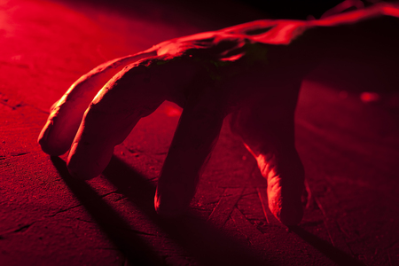 Creepy crawling hand in red light inside a haunted house. Halloween prop. Imagens