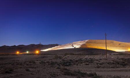 Modern strip mine in the Nevada desert at night.