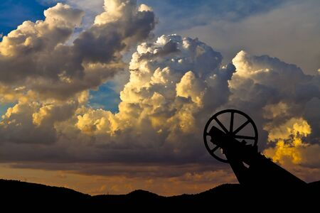 Old mining hoist with dramatic cloud background