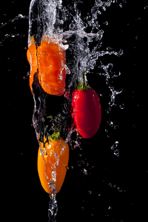Spicy Peppers being splashed with water. Imagens