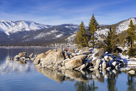 Winter shot of Lake Tahoe with snow on rocks and mountains.  Sand Harbor, Nevada