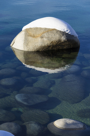 One snow covered boulder in the clean clear waters of Lake Tahoe in Winter.