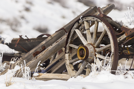 carreta madera: Old broken wagon with wheel in snow and frost with winter background.