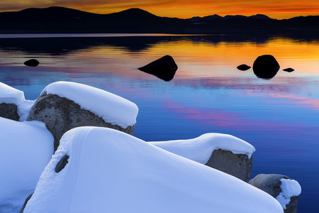 Winter shot of Lake Tahoe with snow on rocks and mountains. Sand Harbor Nevada at Sunset