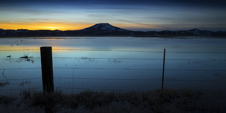 Flooded field at sunset with fence post and barbed wire.  Sierra Valley Wetlands, Northern California. 版權商用圖片