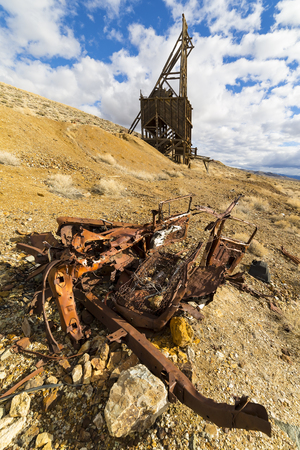 Ghost town mining head frame in the Nevada desert with wrecked car in the foreground.  Sky is blue with clouds.