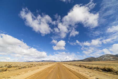 Dirt road in the Nevada desert under blue sky with clouds.  Road is wet dirt and mud. 版權商用圖片