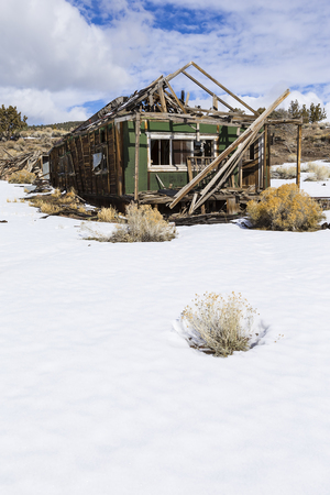the miners: Old weathered Ghost Town buildings in the desert during winter with snow.  Ione, Nevada Stock Photo