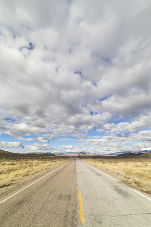Empty rural paved road in the Nevada desert under cloudy skies.