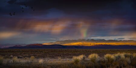 Stormy Sunset with rain and rainbow in the desert with light on mountain range.  Fallon, NV 版權商用圖片