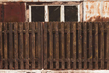 old wooden fence and abandoned old barn window in orange brown tones