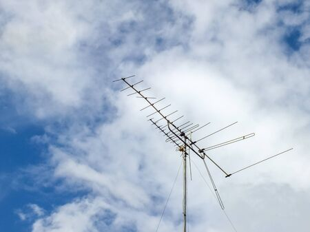 a old tv antenna with blue sky photo