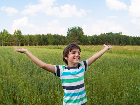 tween boy: happy boy over wheat field in summer day Stock Photo