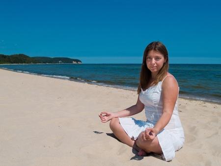 Woman practicing yoga on sea sandy beach photo