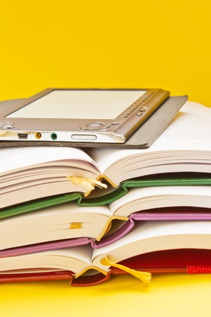 educational research: pile of traditional books and electronic book on orange background