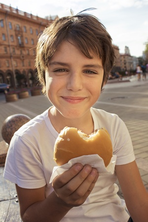 grade schooler: smiling boy with hamburger on city street