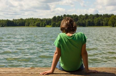 cute young boy: Boy relaxing at  the end of docks, lake Galve, Trakai, Litva