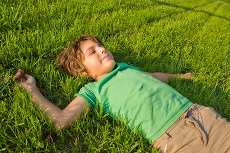 day dreaming: teenager boy relaxing on green grass lawn