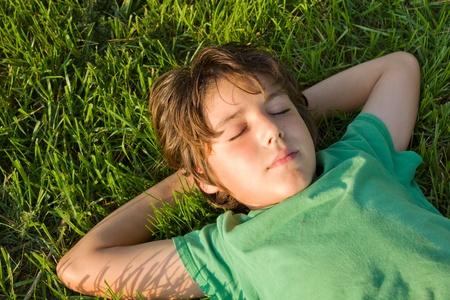 lying in grass: muchacho adolescente relajarse en el jard�n de hierba verde Foto de archivo