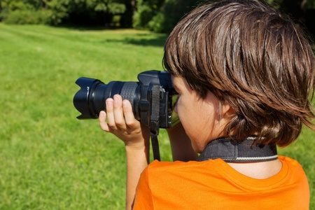 kid taking shots with photocamera in park Stock Photo