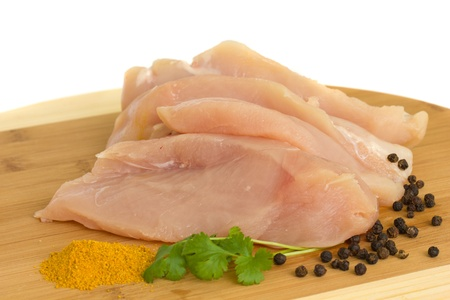 raw chicken breast meat with spices isolated on white