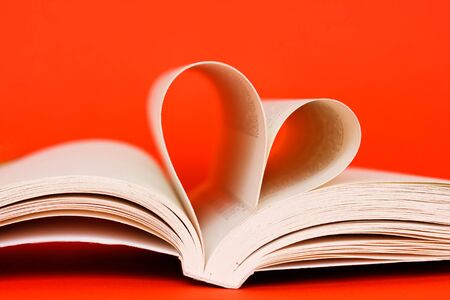 open book with heart of pages on orange background photo