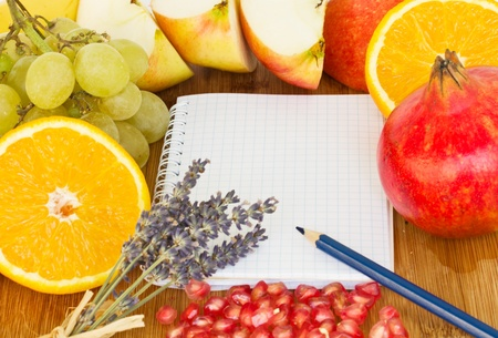 blank notebook for recipes with frame of fruits photo