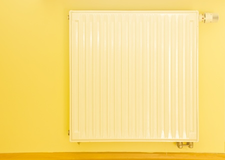 modern heater with thermostat on a yellow  wall photo