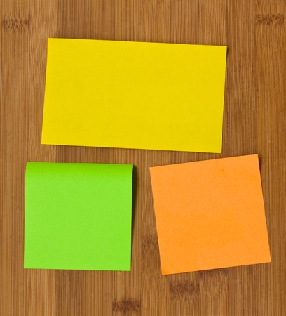 three multicolored post it  notes on wooden board Stock Photo - 11430121