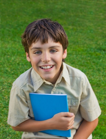 happy school boy  with note book on green grass background photo