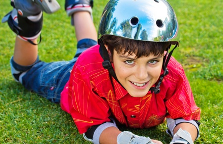 happy boy in roller blades grear laying on grass Stock Photo