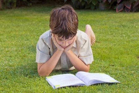 boy  reading book on green grass lawn photo