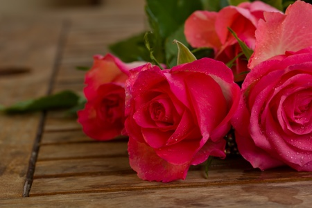 bouquet of pink roses in water droplets on wooden table photo